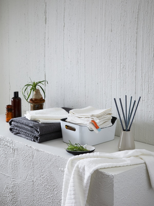 A white bathroom ledge with bathroom accessories, including towels and incense, placed on top.