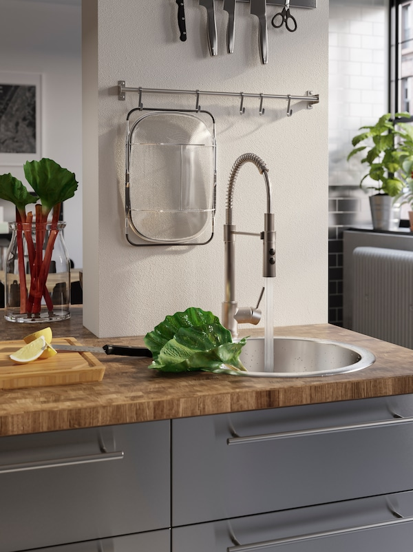 A wooden worktop with an inset sink and a mixer tap that's turned on to wash rhubarb placed in the sink.