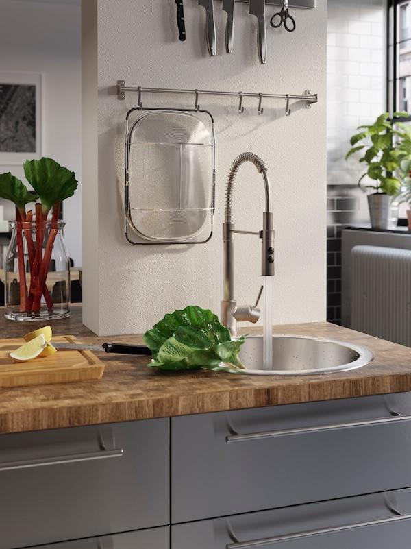 Drvena radna ploča s ugradnom sudoperom i kombinovanom slavinom, za pranje rabarbare u sudoperi.