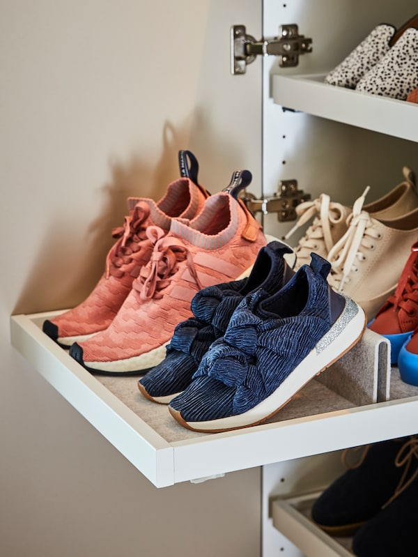 Un armario con tres estantes, cada uno tiene un accesorio para zapatos KOMPLEMENT con bandeja extraíble y varios pares de zapatos.