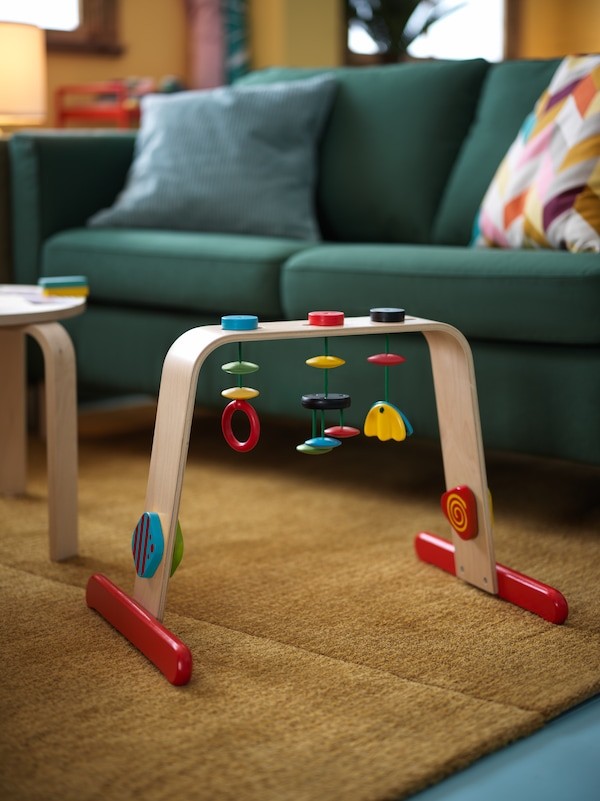A living room interior with a LEKA birch baby gym placed on a rug beneath a PÄRUP dark-green two-seat sofa.