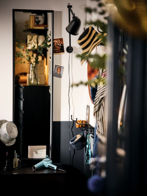 Ecke eines Raumes mit einem schwarzen NISSEDAL Spiegel und einer wandmontierten SKURUP Leuchte zwischen verschiedenen Dekogegenständen.