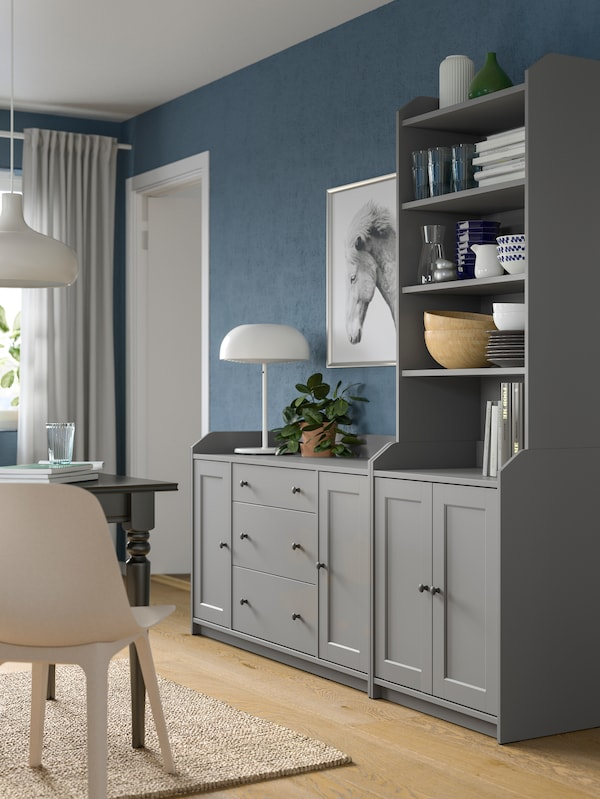 A grey HAUGA combination of a chest of drawers side by side with a high cabinet, standing by a living-room wall.
