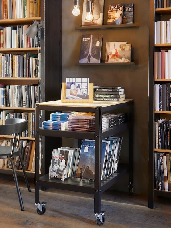 Ein Tisch mit Büchern auf der Tischplatte und auf der Ablage darunter. Die Präsentation setzt sich im Bücherregal und auf den Wandregalen dahinter fort.