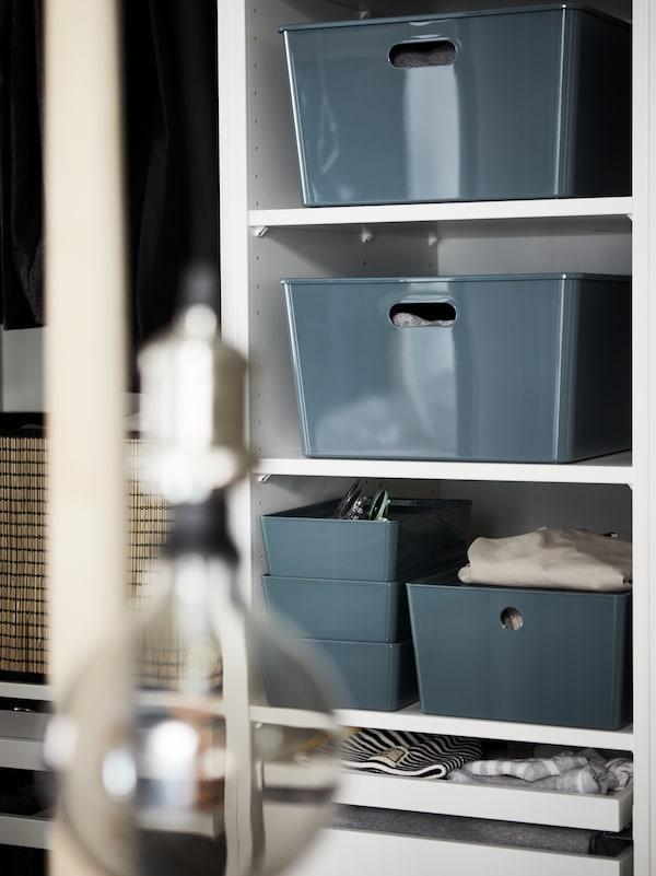 Egy JÄLLBY/ROLLSBO függőlámpa mögött fehér, nyitott polcokon türkizkék KUGGIS tárolódobozokban ruhák vannak elhelyezve.