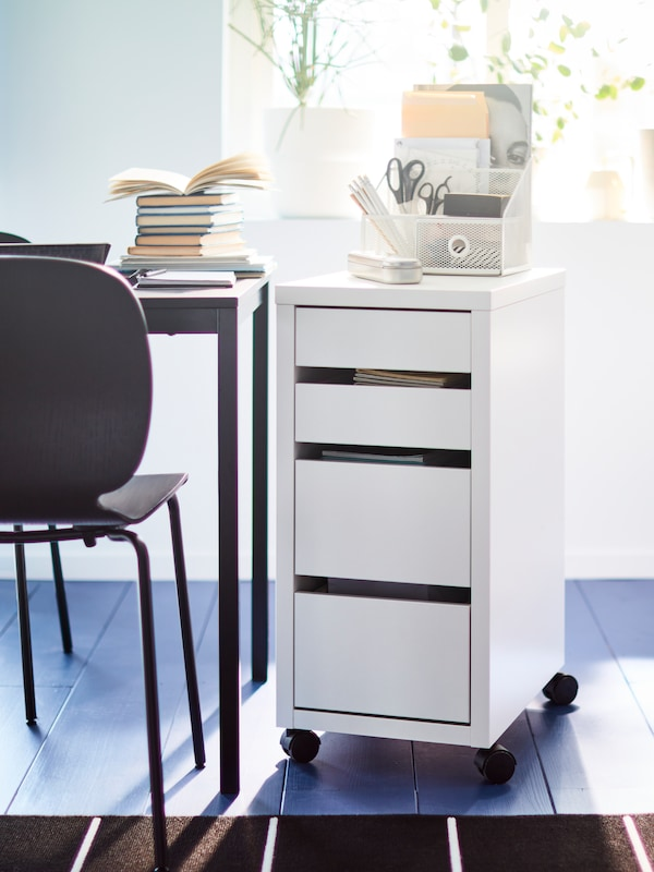 A white storage cabinet with office supplies on it, a desk with books on it and a black chair, plants in the window.