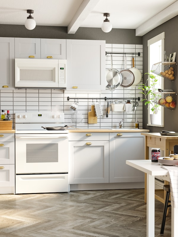 A white KNOXHULT kitchen with white-tiled and gray walls, two black rails with pans and cooking utensils.