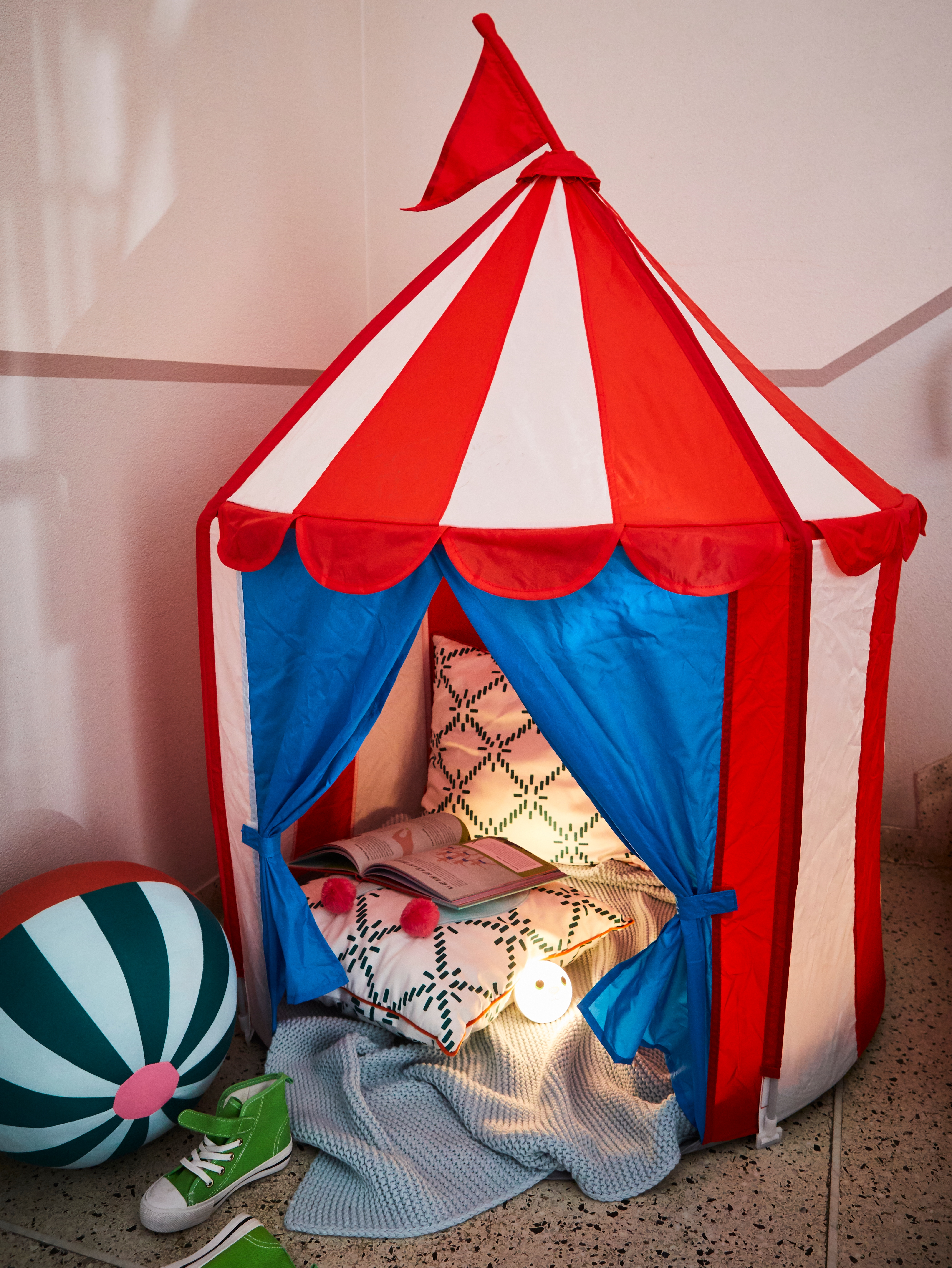 A red and white striped CIRKUSTÄLT child tent with blue open doors, filled with two cushions and an open book.