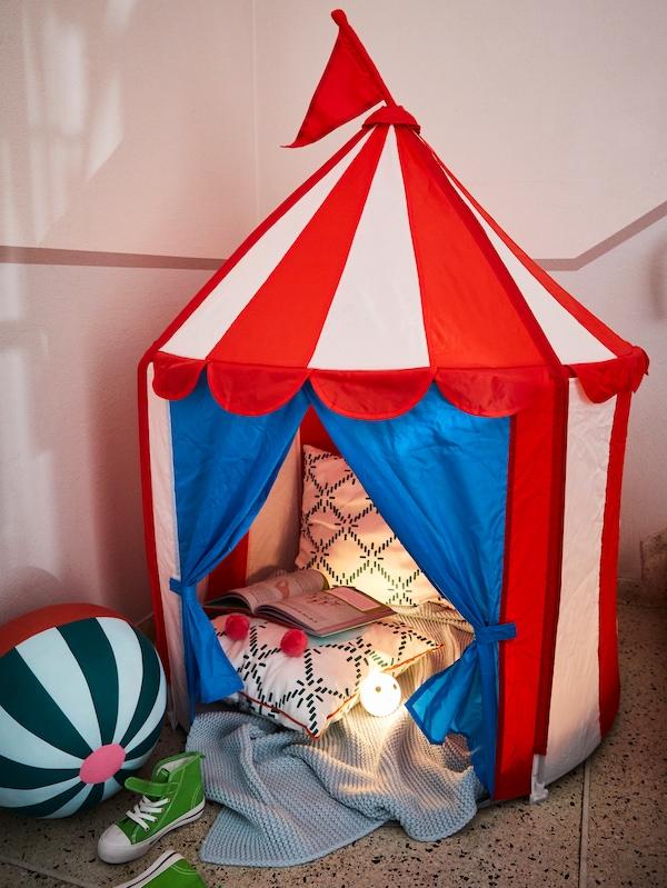 红白条纹的CIRKUSTÄLT 勒克斯塔 儿童帐篷,蓝色帐门打开。里面放着两个靠垫和一本打开的书。
