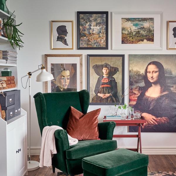 En grøn STRANDMON lænestol i velour med tilhørende fodskammel. En rød pude og et rødt bord og en masse renæssancemalerier på væggen.