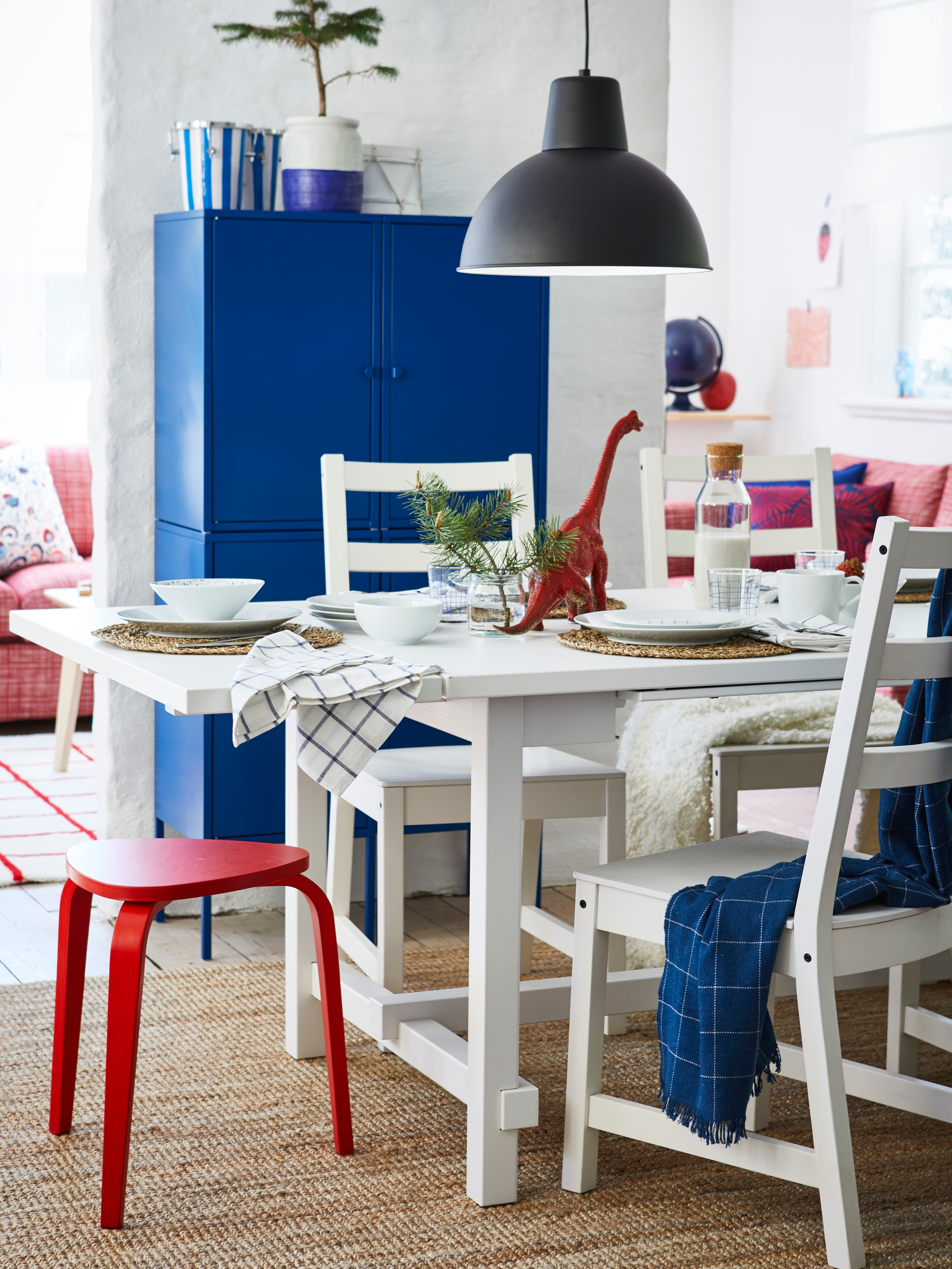 A NORDVIKEN extendable table in white, playfully set for a meal, with chairs and a blue storage unit in the background.