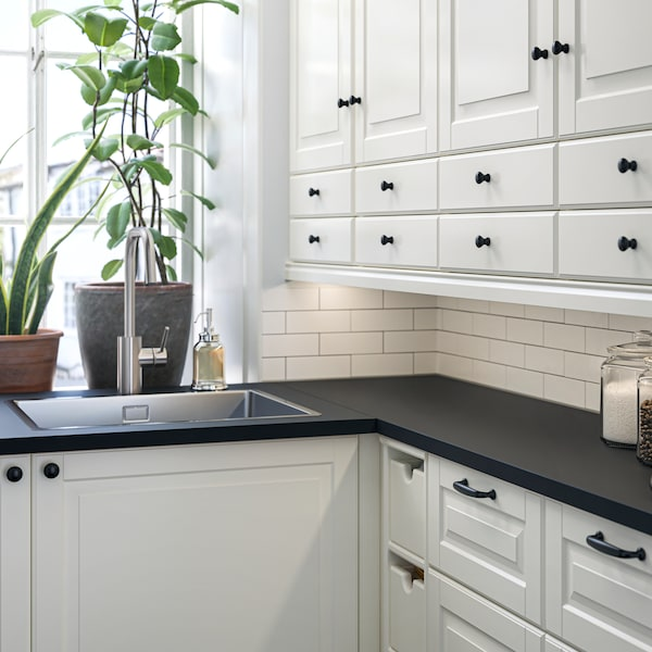 Eine Küche mit BODBYN Fronten und Schränken in Elfenbeinweiß. Auf der Fensterbank neben der Spüle sind zwei Pflanzen zu sehen.