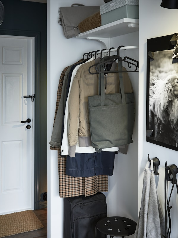 An odd nook with a white clothes bar with jackets and coats hanging, a black cabin bag, a shelf with boxes and bags.