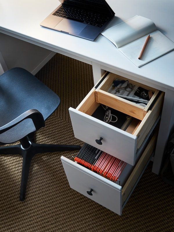 A white desk with a laptop and a notebook, the drawers open with diverse items in them, and a chair.