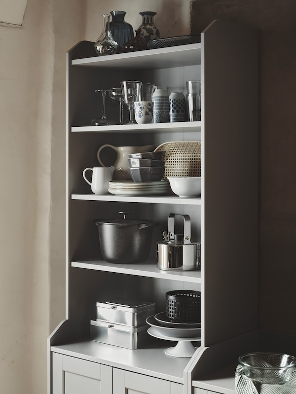 A HAUGA high cabinet with dinnerware and cookware on the shelves, including STRIMMIG bowls and a VARDAGEN pot with lid.