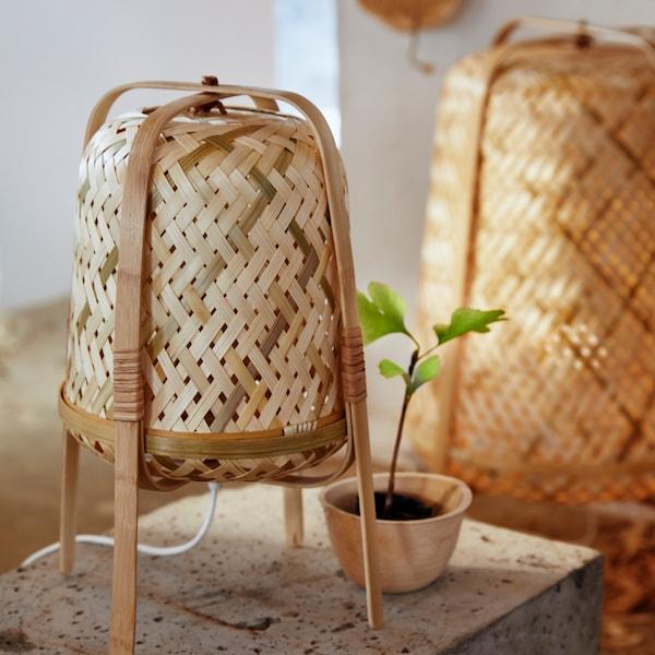 화이트 케이블이 달린 대나무 탁상스탠드가 놓인 보조테이블, 녹색 화초를 담은 작은 화분.