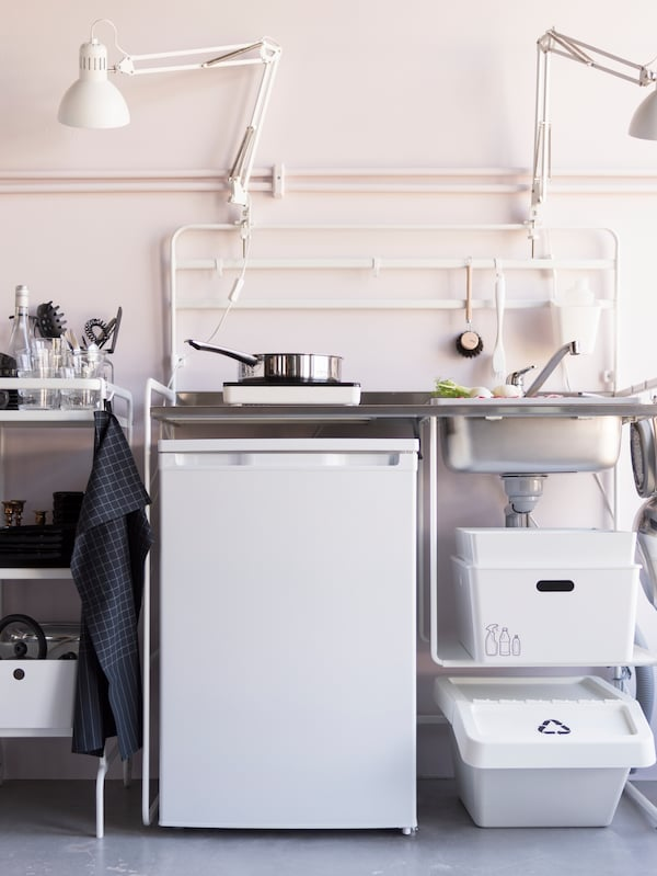A small white mini kitchen with a portable induction hob and a small fridge. A white trolley stores kitchen supplies.