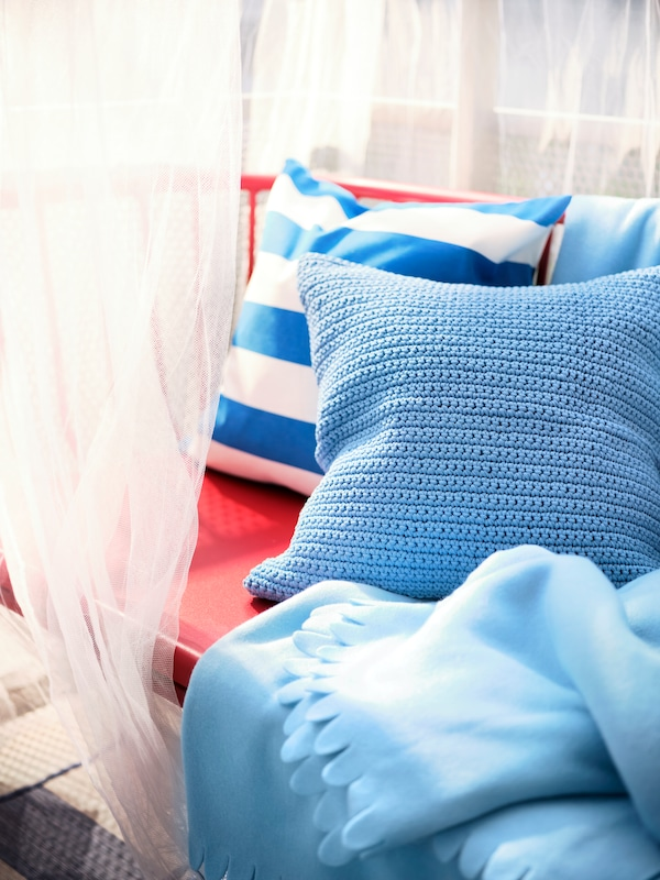 Cushions in a light blue in/outdoor SÖTHOLMEN cover and a blue/white FUNKÖN in/outdoor cover sit on an outdoor BRUSEN sofa.