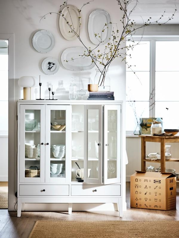 Une pièce dotée de murs blancs et d'un plancher meublée d'une vitrine IDANÄS, des assiettes ornant le mur au-dessus d'elle.