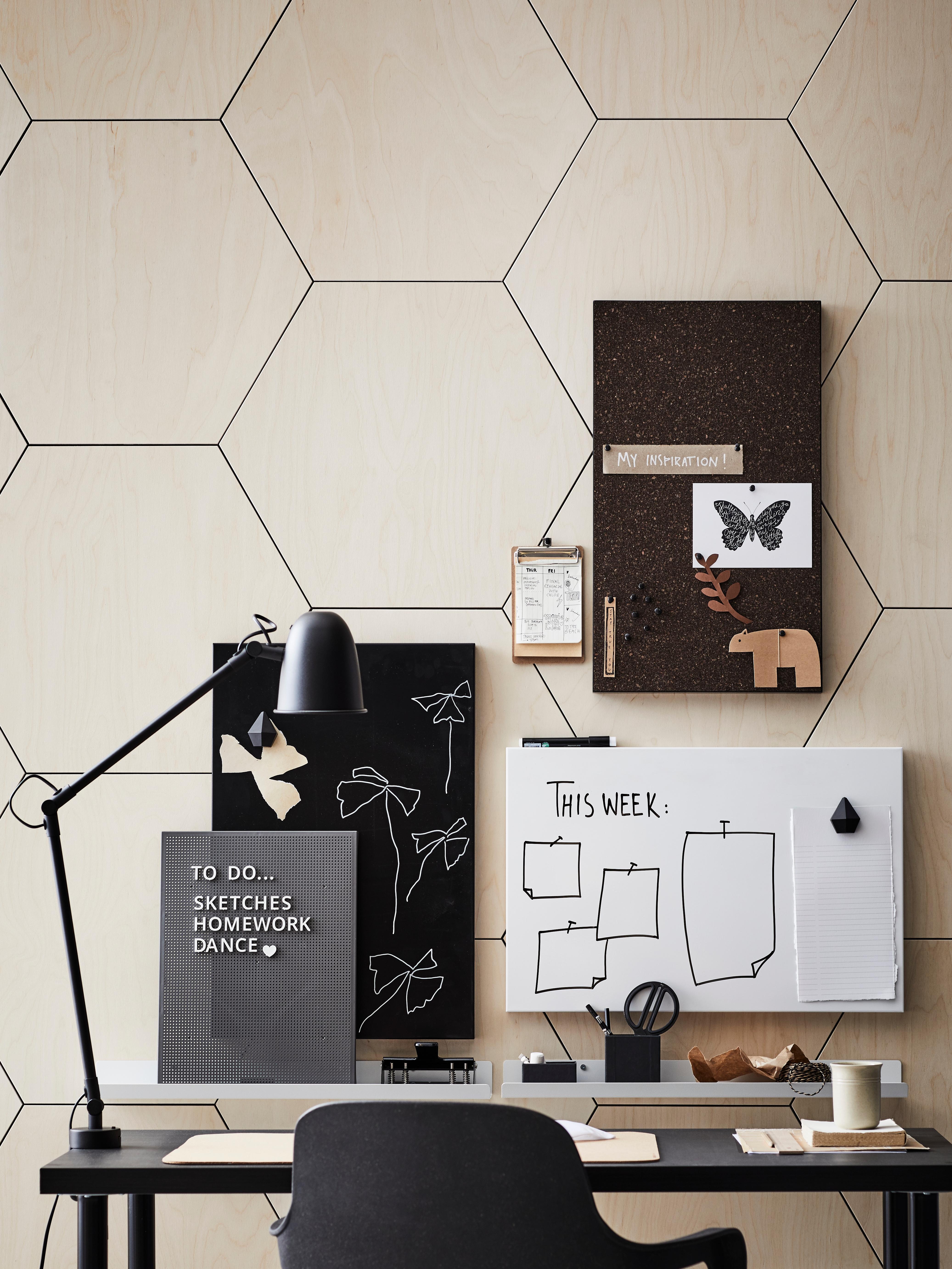 Radni stol i stolica ispred zida s drvenim uzorkom saća s pločom za napomene i SVENSÅS rupičastom pločom sa slovima i radnom lampom.