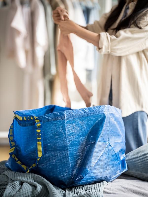 Un sac FRAKTA bleu à moitié plein placé sur un lit, avec une femme pliant des vêtements en arrière-plan.