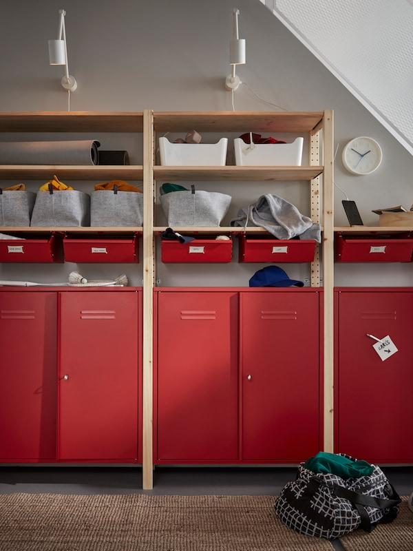 Une étagère IVAR avec des armoires et tiroirs rouges qui contient des paniers et des articles ménagers, avec deux appliques au-dessus.