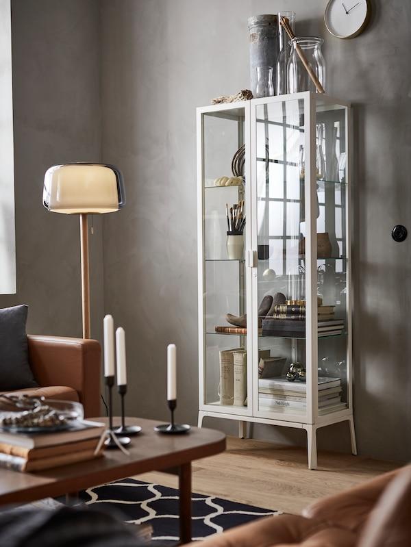 Eine IKEA MILSBO Vitrine in Weiss enthält hier verschiedenste Gegenstände zur Präsentation. Hinzu kommen eine Standleuchte und ein Tisch.