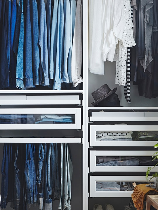 An open PAX wardrobe with hanging clothes, shelves and KOMPLEMENT drawers with framed glass fronts inside.