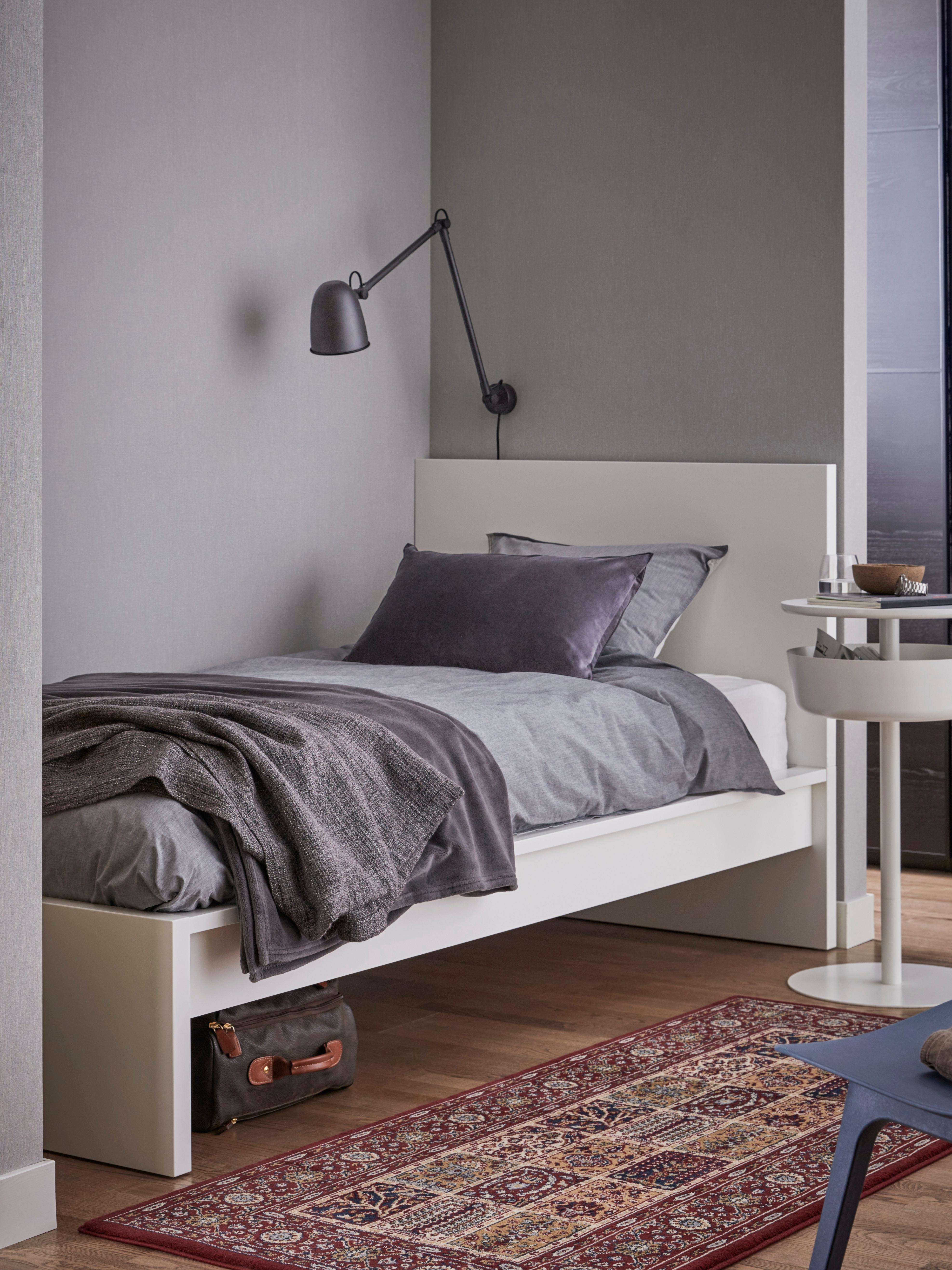 Struttura letto alta MALM bianca, copripiumino grigio, plaid grigio scuro e lampada da parete grigio scuro in una stanza con le pareti grigie.