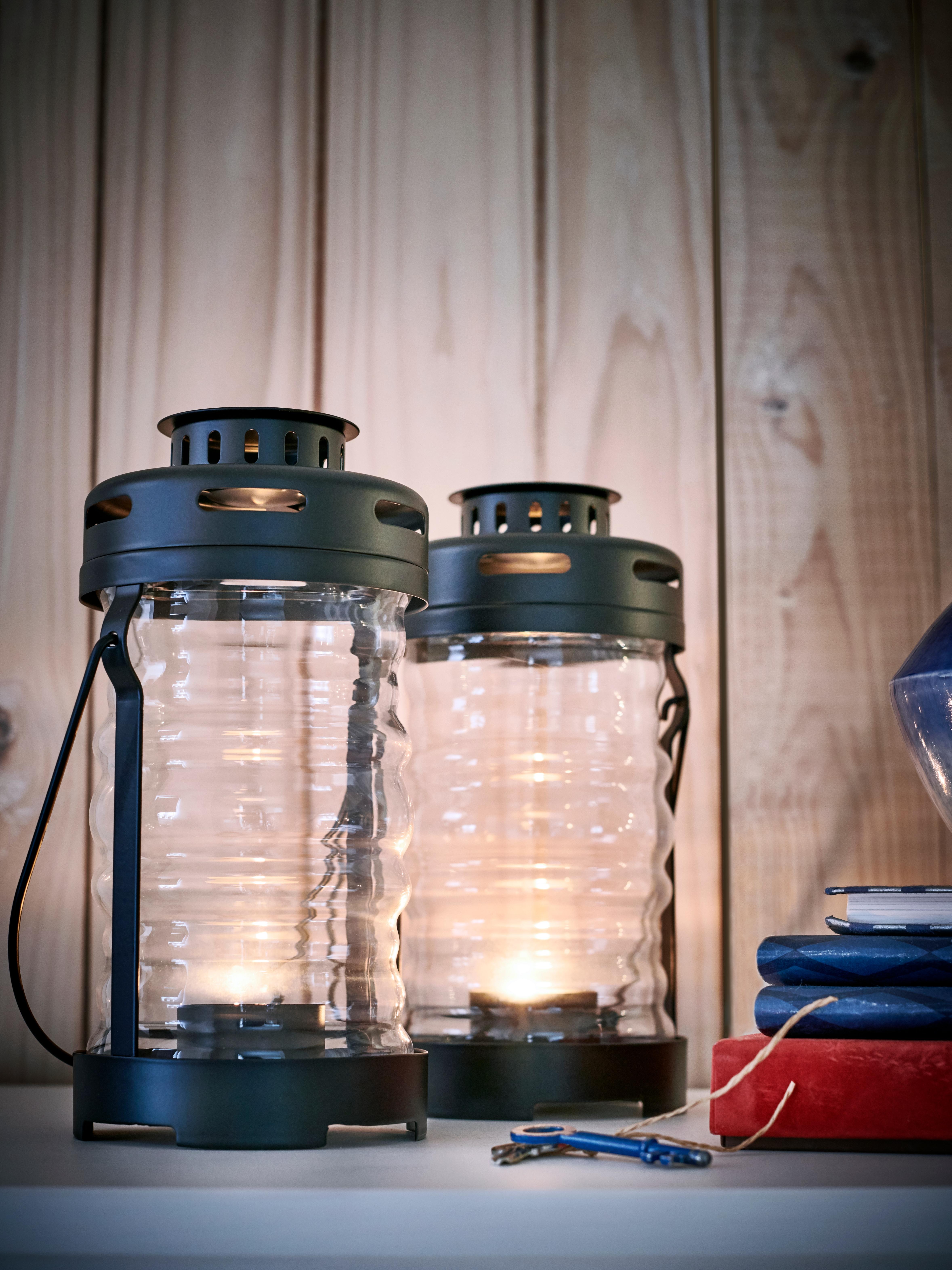 Dva GLIMRANDE fenjera na polici; svaki je s upaljenim lučicama.