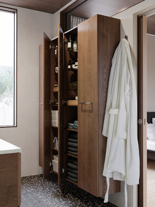 Højskabe med trælåger fastgjort til en væg, hvori man kan se håndklæder, toiletsager og bokse arrangeret på nydelig vis.
