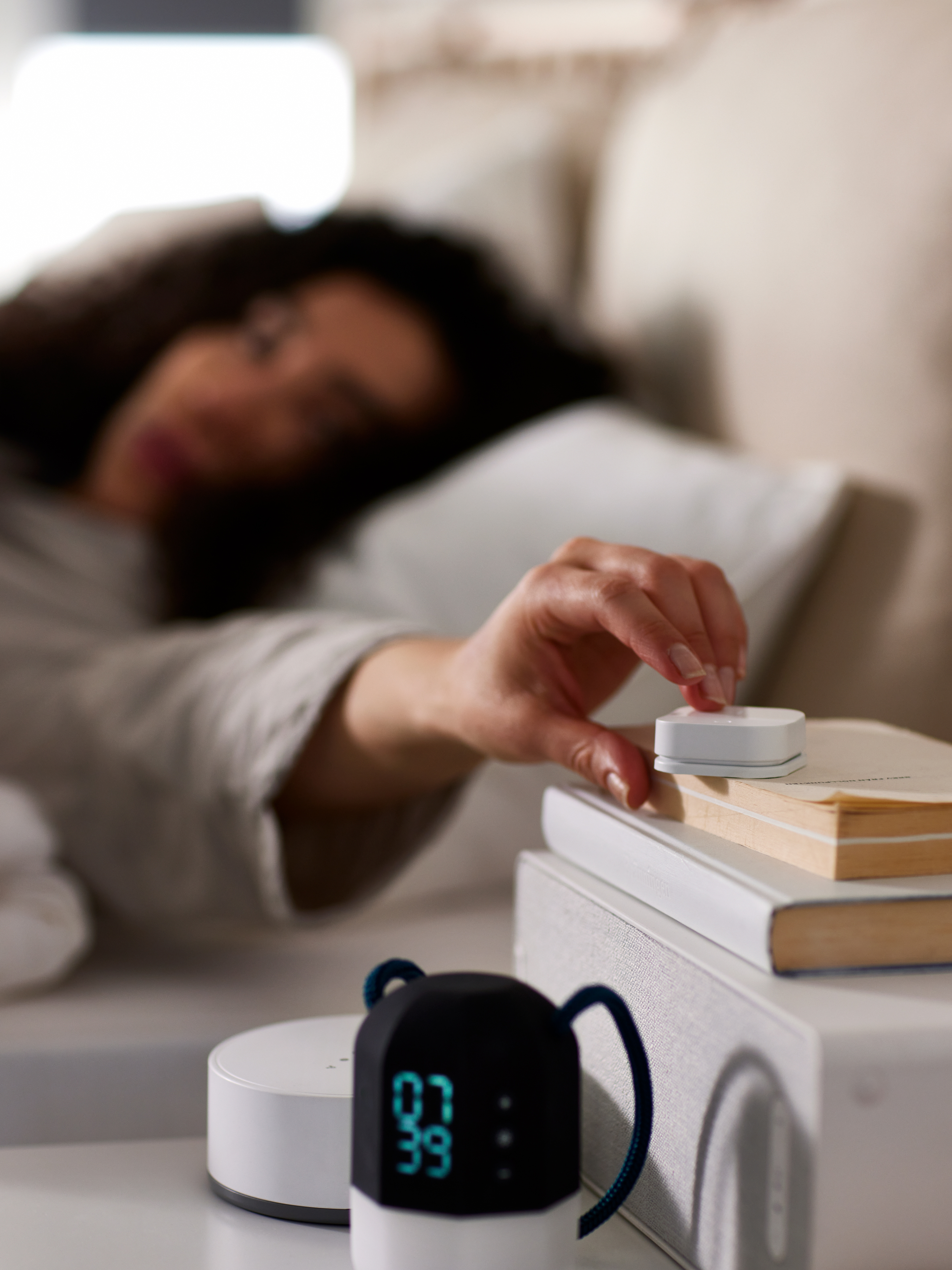 A woman lying in bed pushing a TRÅDFRI wireless dimmer on top of some books and a WiFi speaker on a white bedside table.
