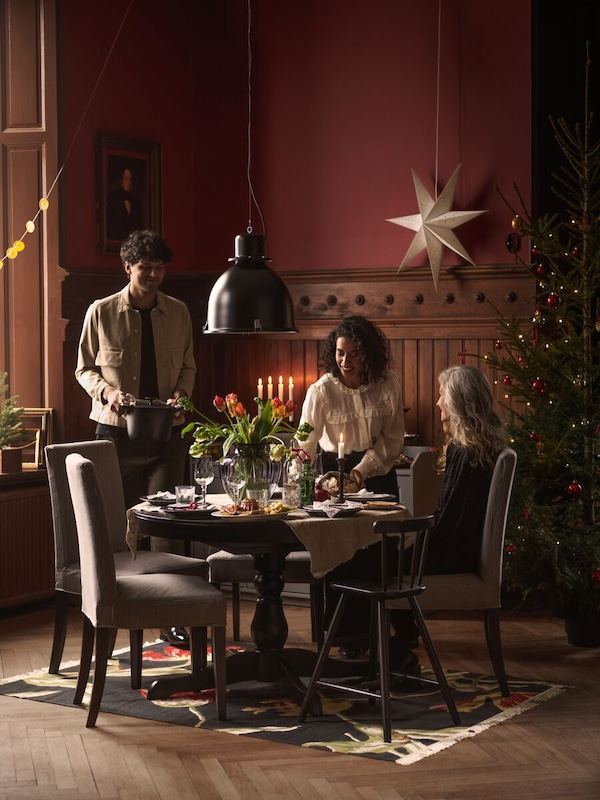 Small gathering of 3 friends sitting around small dining table setting in dark coloured room. Room is seasonally decorated.
