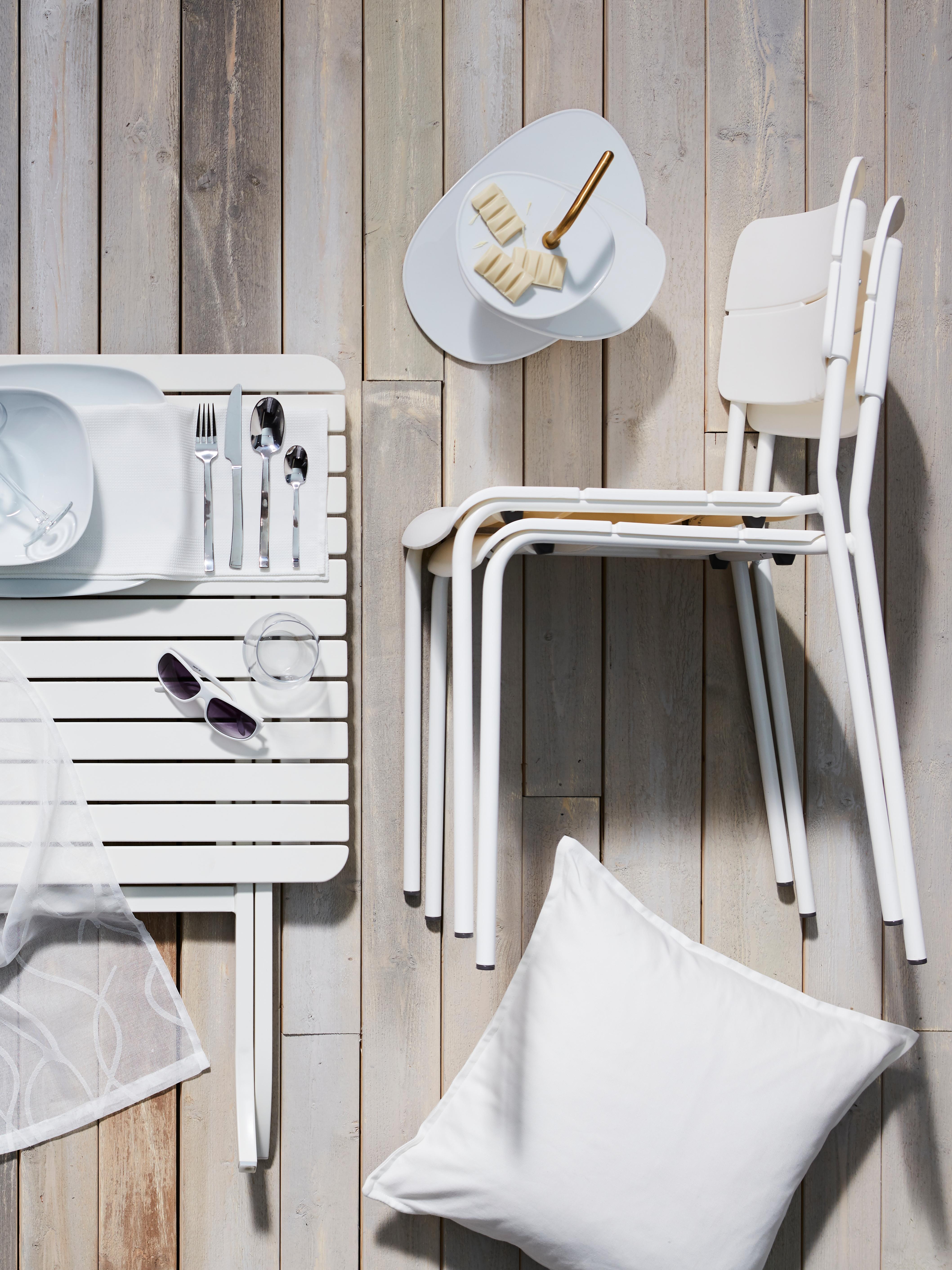 Bijeli MÄLARÖ sklopivi vanjski stol na drvenom podu pokraj bijelih stolica i bijele ukrasne jastučnice.