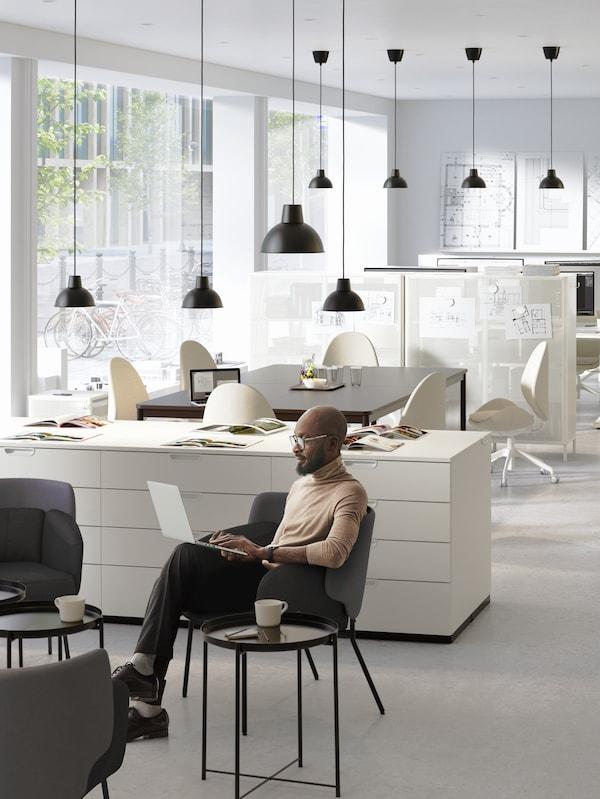 Moški v pisarni sedi na stolu z prenosnikom, skodelica kave na klubski mizici, v ozadju prostor za shranjevanje in svetilke.