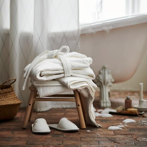 Banco pequeno em madeira com textil branco em cima e chinelos brancos no chão.