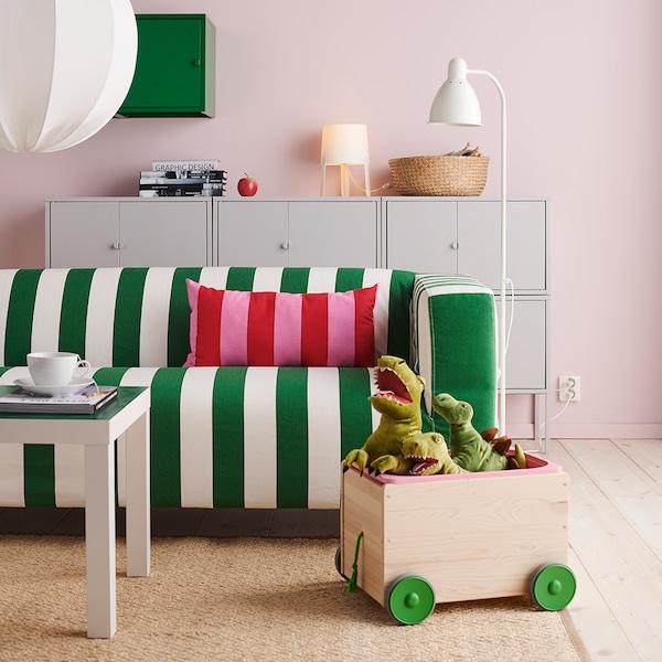 Sofá KLIPPAN às riscas verde e branco numa sala com paredes rosas e uma almofada às riscas vermelho e rosa. No chão uma caixa de madeira com brinquedos.
