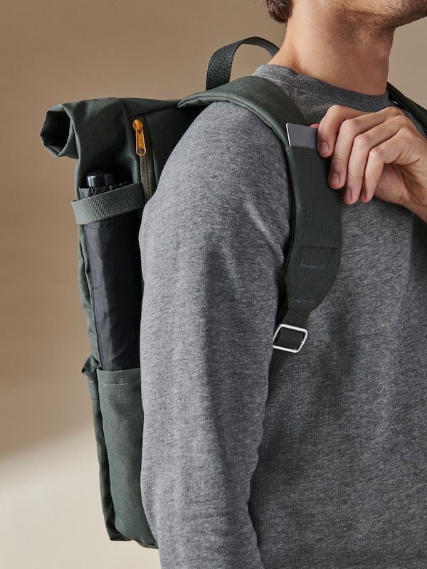 A man carrying a green DRÖMSÄCK backpack, taking out a card from the card slot on one of the shoulder straps.