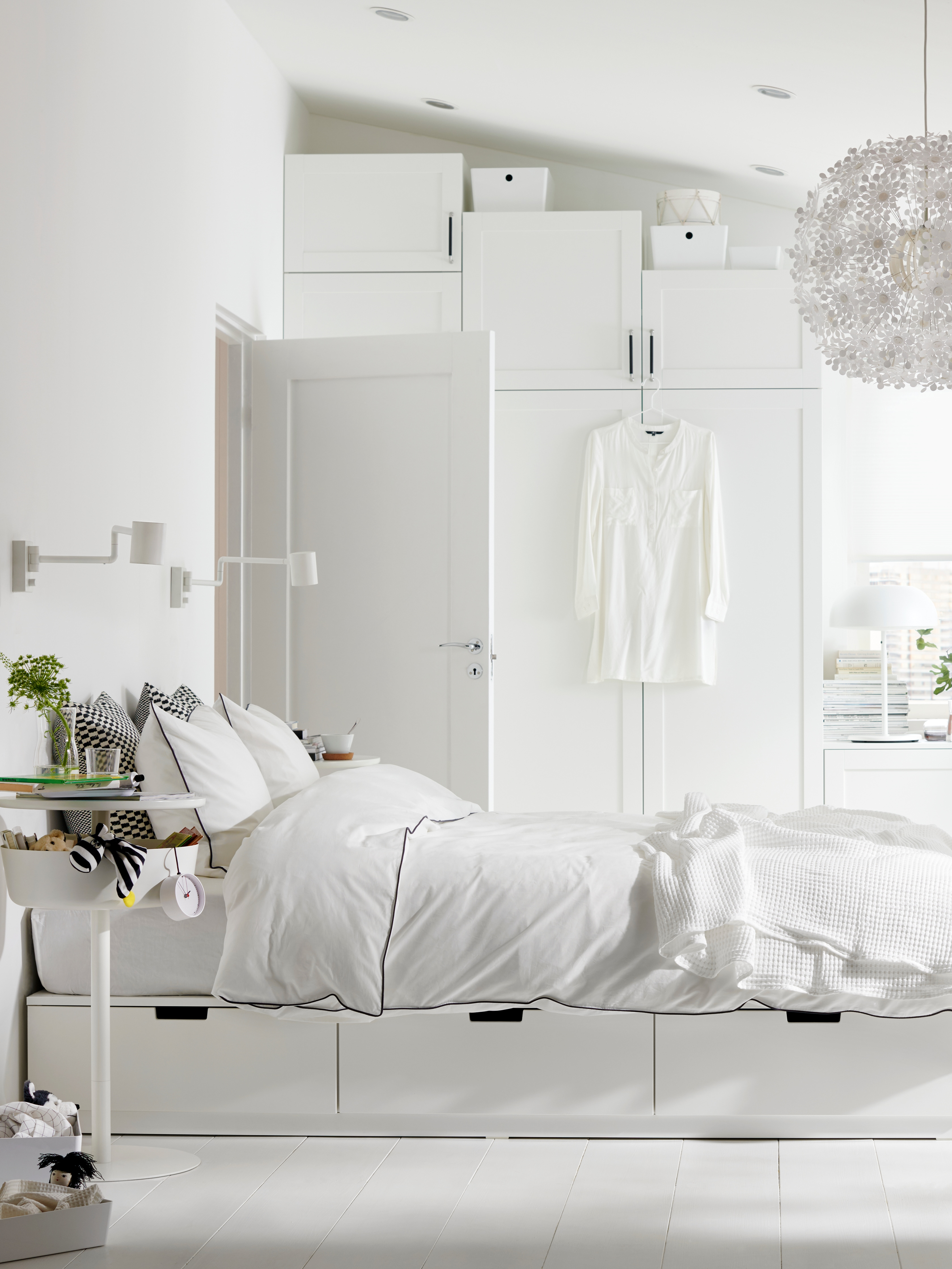 NORDLI bed frame in a bright bedroom with white quilt cover and pillowcase and a white airy-shaped pendant lamp.