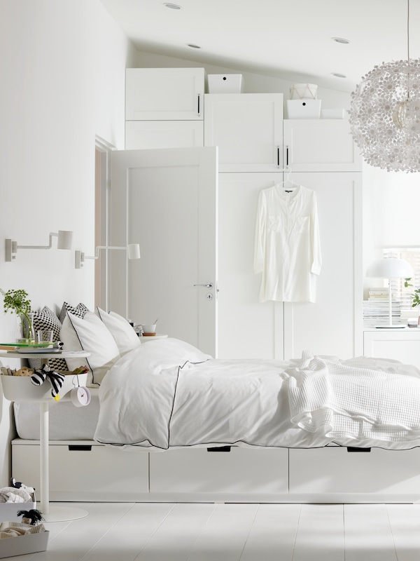 A bright, white bedroom with a NORDLI bed with storage with KUNGSBLOMMA bed linen and a lot of other white furniture.