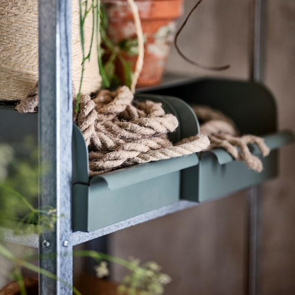 A shelf in a HYLLIS shelving unit with two grey-green/metal REJSA boxes holding bits of rope. A flowerpot stands on one box.