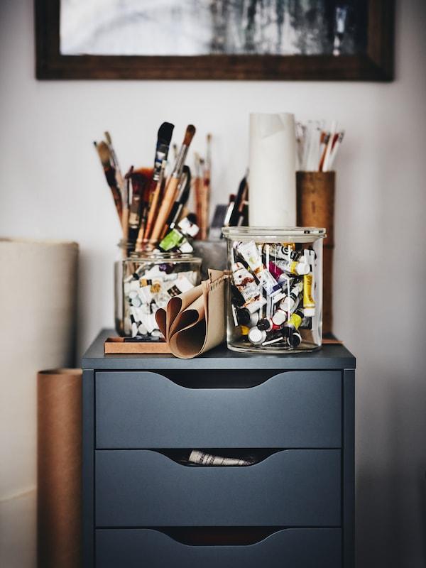 Bloc-tiroirs ALEX en gris-turquoise sur lequel sont rangées toutes sortes de fournitures artistiques.
