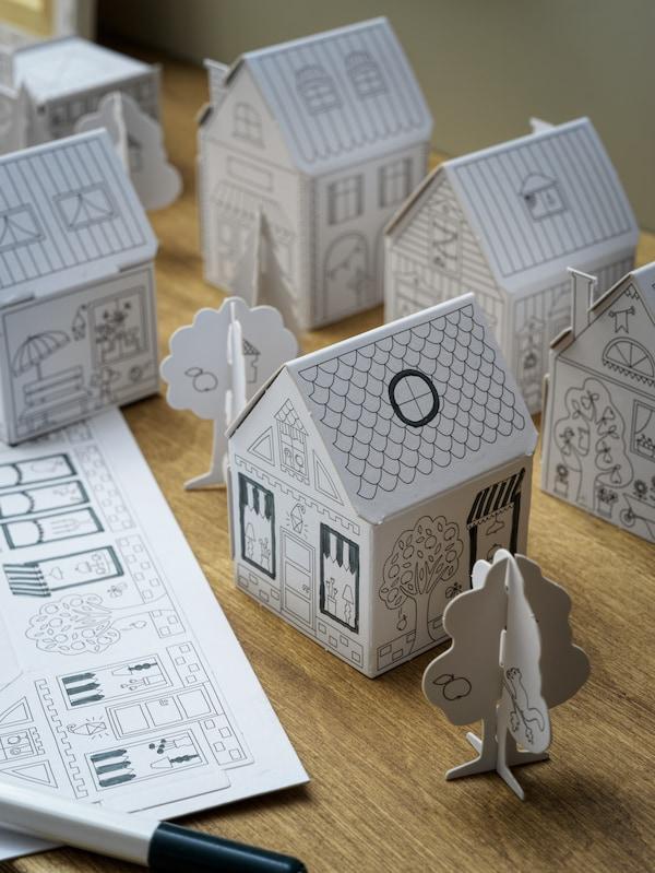 Détails du gabarit ville en carton MÅLA avec de nombreuses maisons et des arbres différents en carton sur une surface en bois.