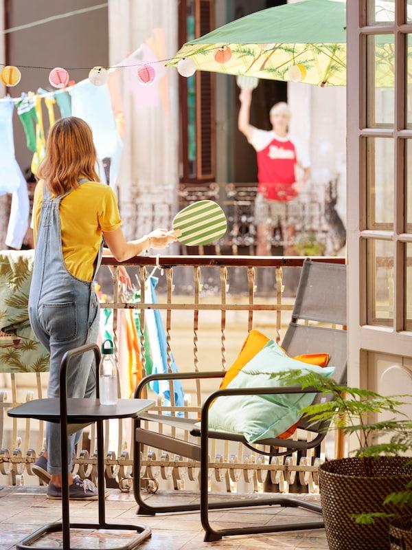Grannar mittemot varandra på sina balkonger vinkandes, med sommarens kollektion SOLBLEKT där utemöbler och textilier samsas för en tropisk känsla.
