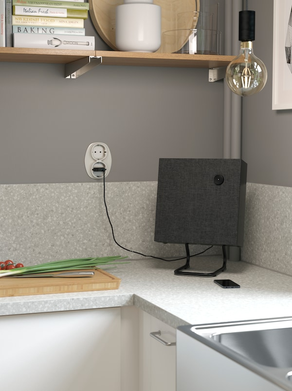 Prikaz malog kockastog crnog zvučnika u kutu sive kuhinjske radne ploče pored daske za rezanje.