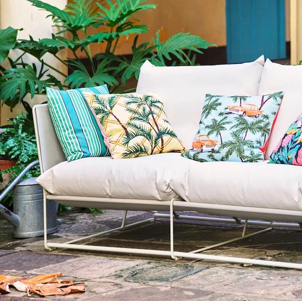O canapea de interior/exterior HAVSTEN este așezată în exterior. Perne suplimentare cu diferite modele colorate sunt așezate pe canapea.
