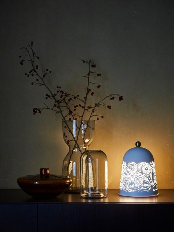 Na komodi se između dvije niske vaze nalazi visoka ukrasna vaza puna jesenskog raslinja, a pored njih stoji i lampa inspirirana prirodom.