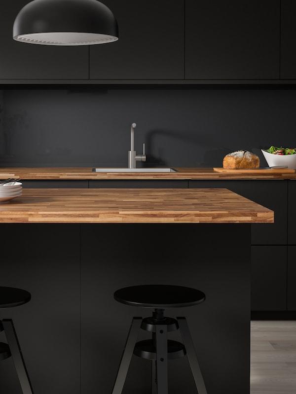 Prikaz tamnosive kuhinje s PINNARP kuhinjskim radnim pločama od orahovog furnira, dva crna DALRFED barska stolca i kuhinjskom lampom.