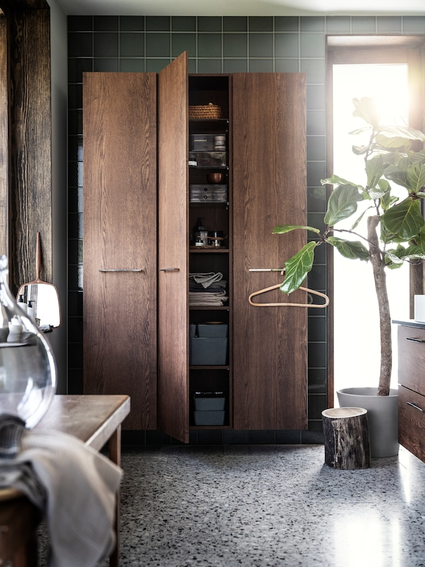 A bathroom with GODMORGON wall  unit in dark brown wood, with middle dor open showing organised shelving  and a potted ficus on the floor.