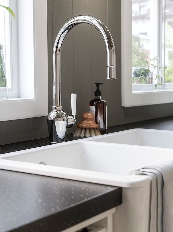A close-up of a white kitchen sink with a shiny chrome-plated mixer tap.